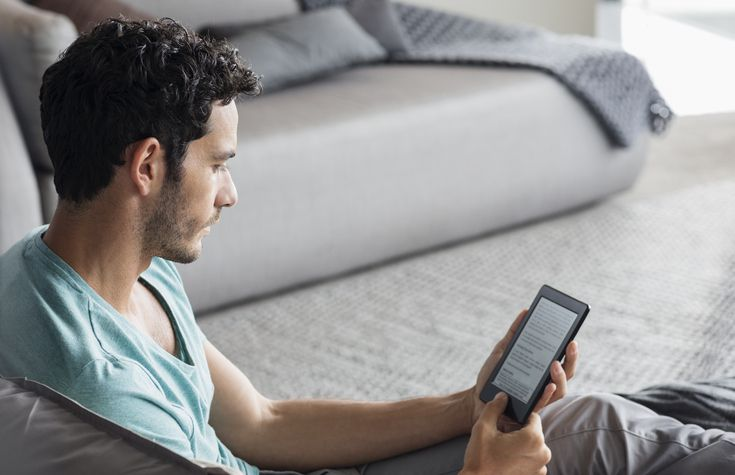 Man using digital tablet in bedroom
