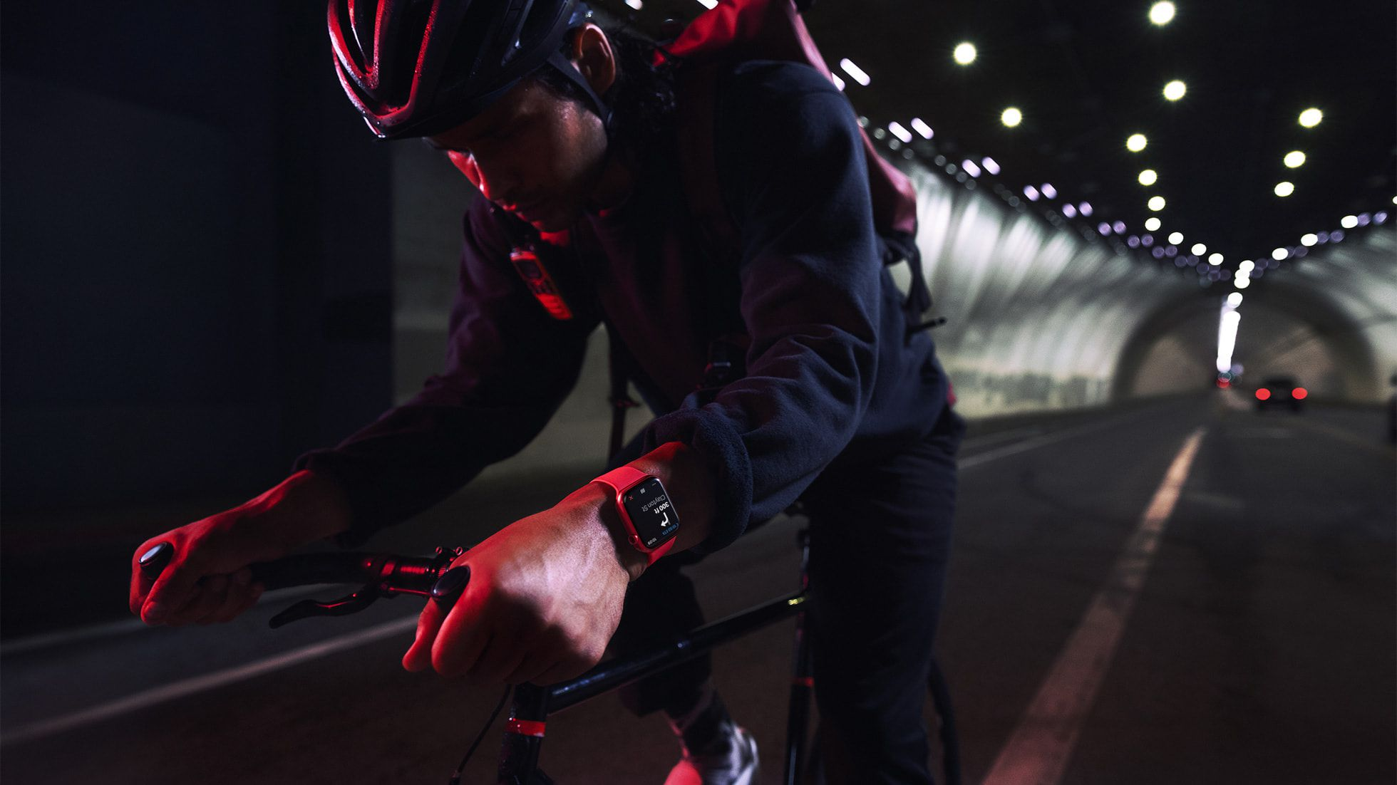 Someone riding a bike in a tunnel wearing the (PRODUCT)RED Apple Watch 7.