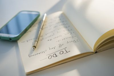 Notebook with list of things to do along with pen and smartphone