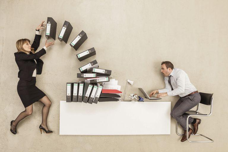 Woman throwing binders on man's desk.