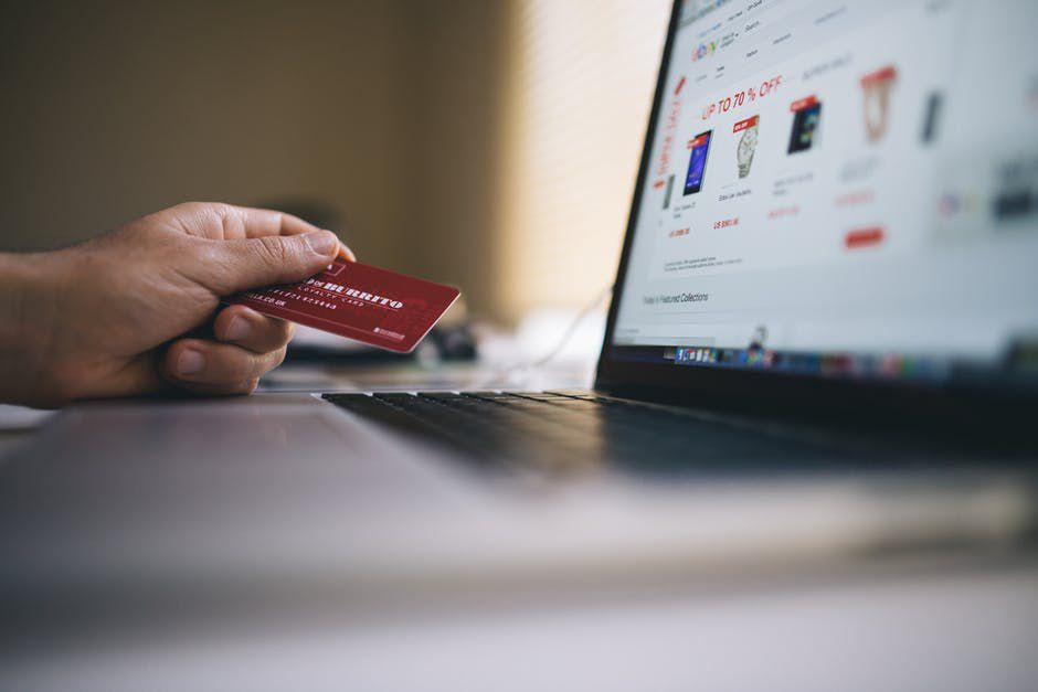 Hand holding a credit card in front of an open laptop