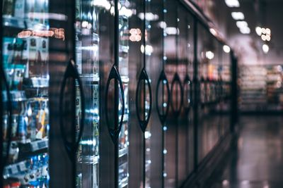 A supermarket aisle alongside a long row of food refrigeration units.