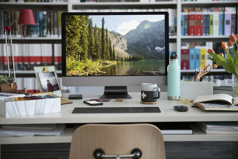 Desktop computer with photo of lake and trees sitting on desk in office