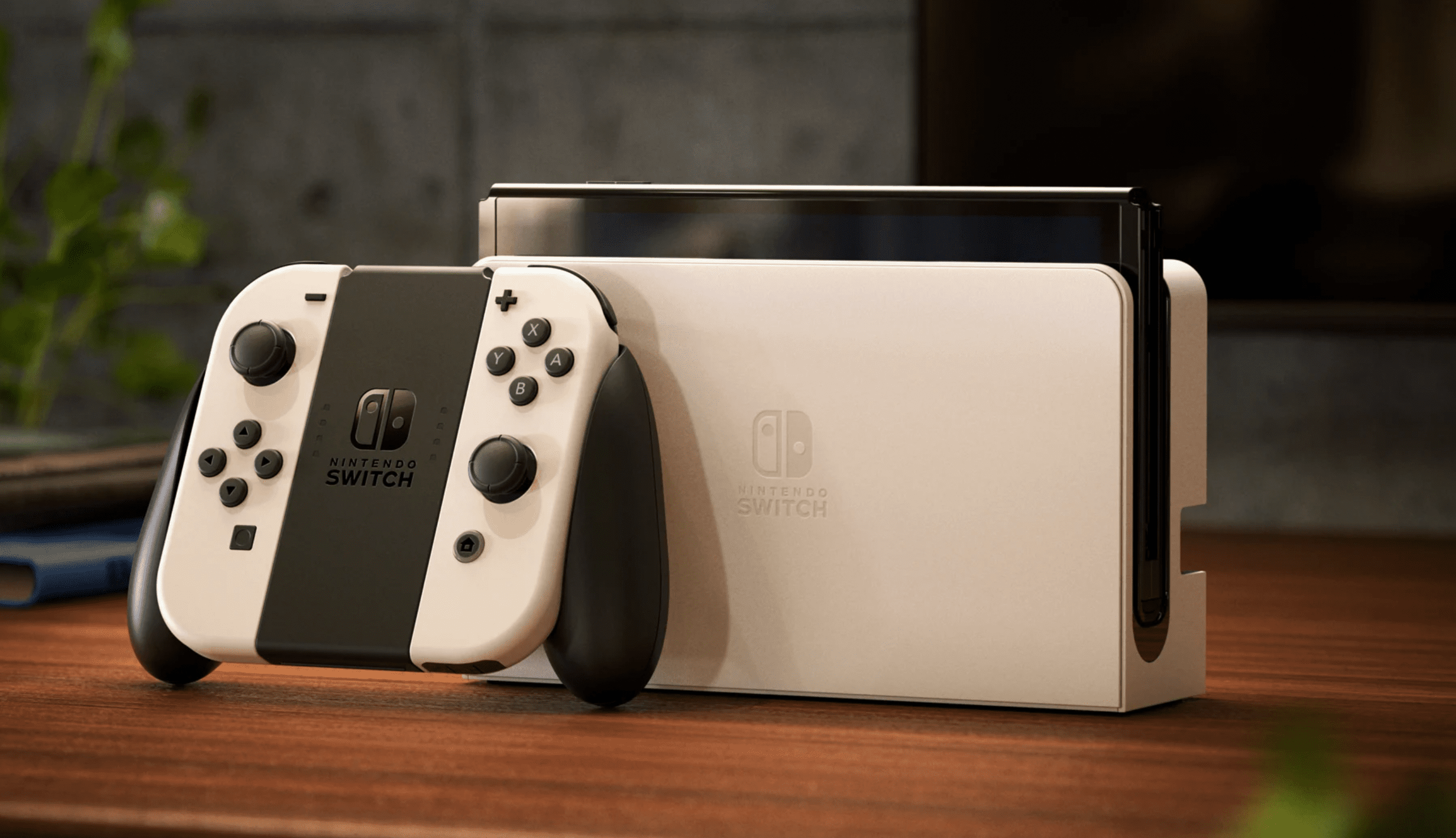 Nintendo Switch OLED Model in white and sitting on a wood desk