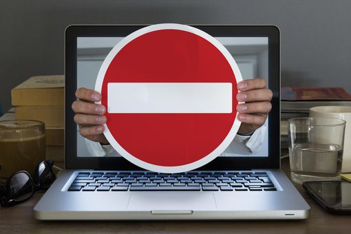 No entry sign appearing out of laptop computer