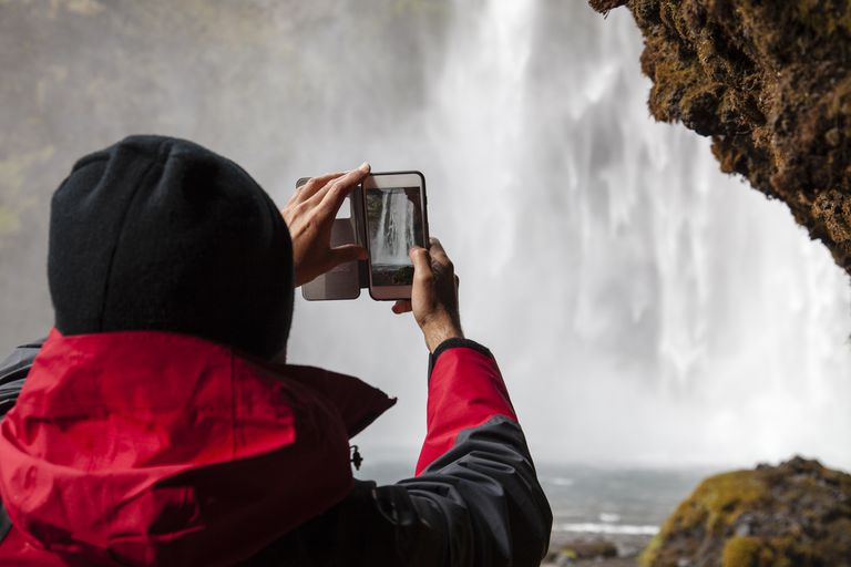 Tourist filming Skogafoss with smartphone
