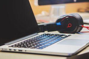 A pair of Beats headphones next to a laptop