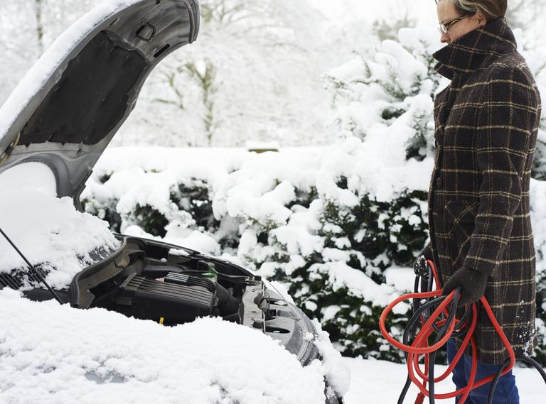 Man holding jumper cables in snow in front of car with hood up