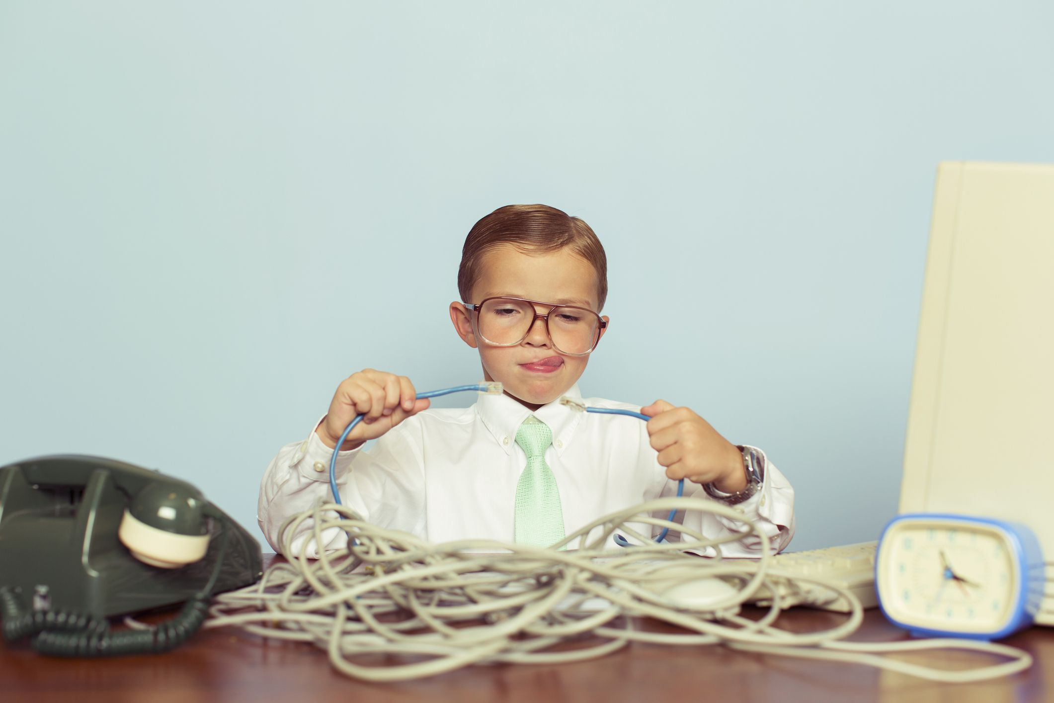 kid working with a large pile of tangled internet cables on his desk