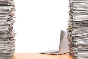 Stacks of newspapers with laptop
