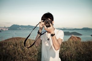 Man taking photo outside with DSLR camera