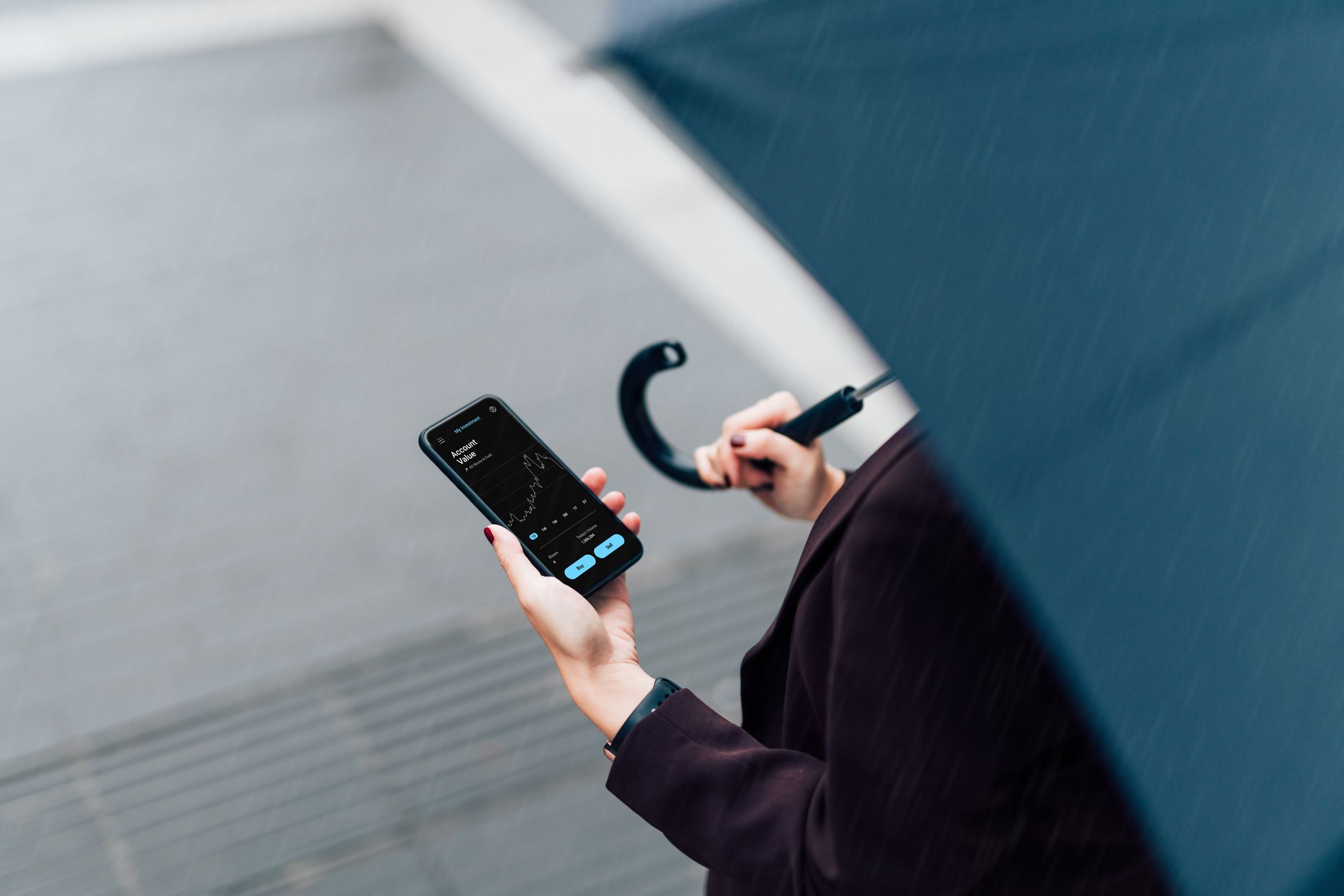 Someone holding an umbreall in the rain while also looking at a smartphone.
