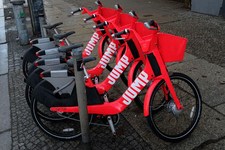 A photo of four, red, electric Uber Jump bikes all parked next to each other on a street.