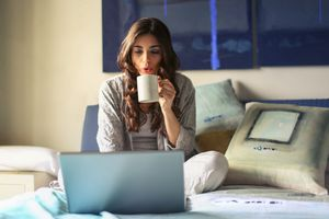 A woman sitting on a bed drinking from a mug.