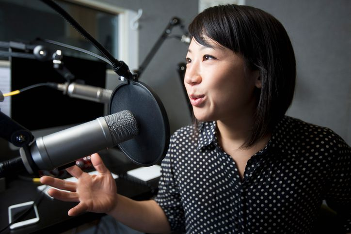 Podcaster speaking into a microphone.