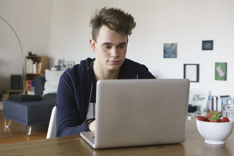 Teenage boy using laptop on table at home