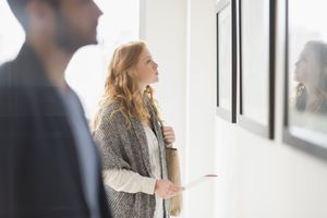 Woman looking at art for sale hanging on a wall.