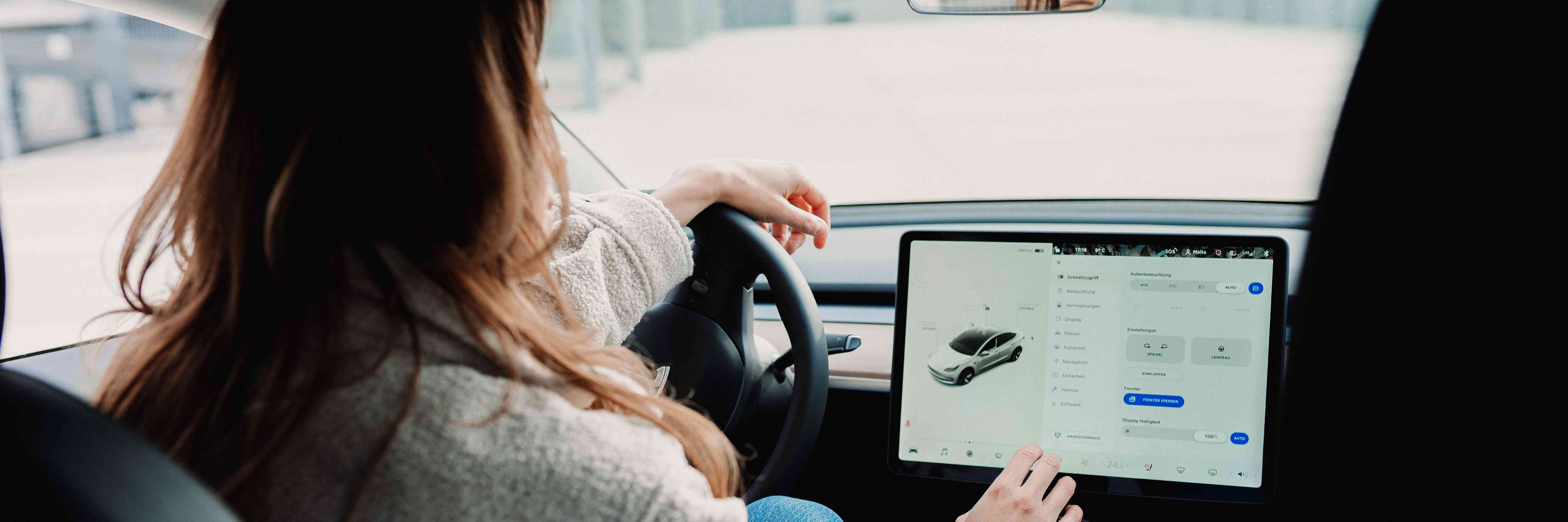 Woman looking at a display unit inside an electric vehicle