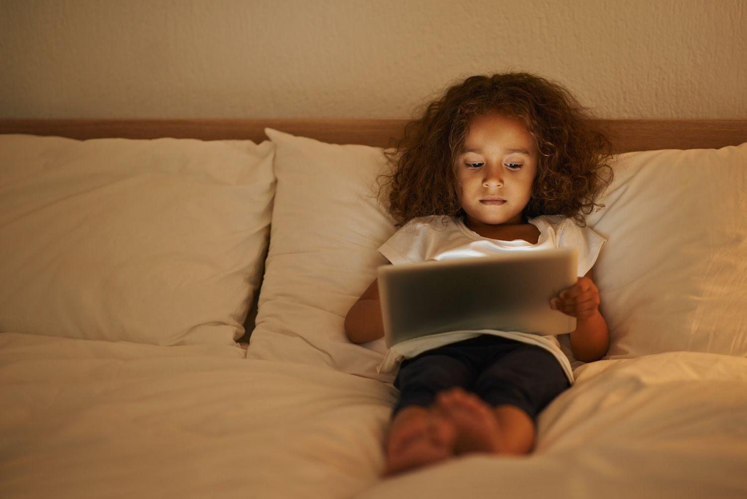 Girl reading on a tablet while in bed