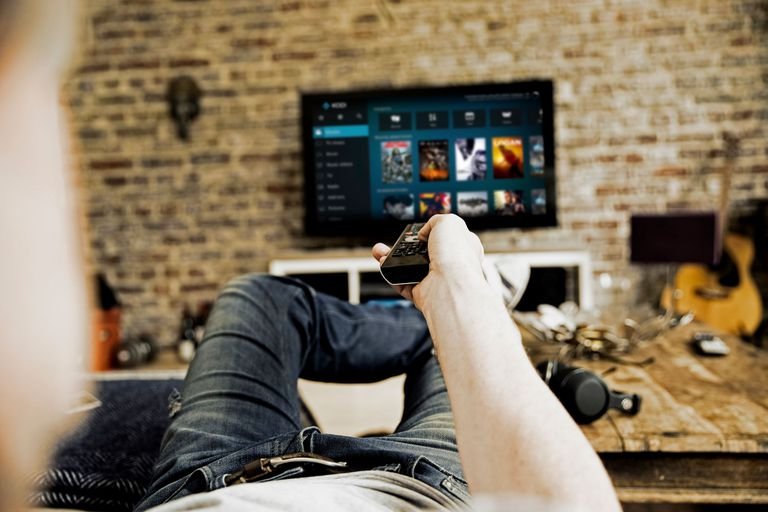 Photograph depicting a man watching television on the couch with Kodi's interface displayed on-screen.