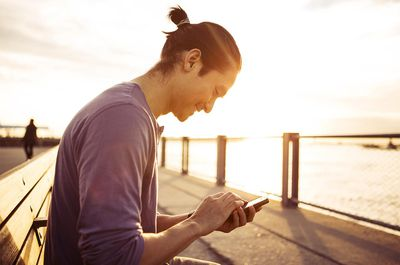 Remote Worker Using Smartphone In Park At Sunset