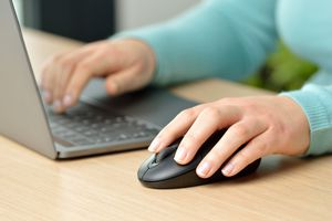 Someone using a mouse with their left hand.