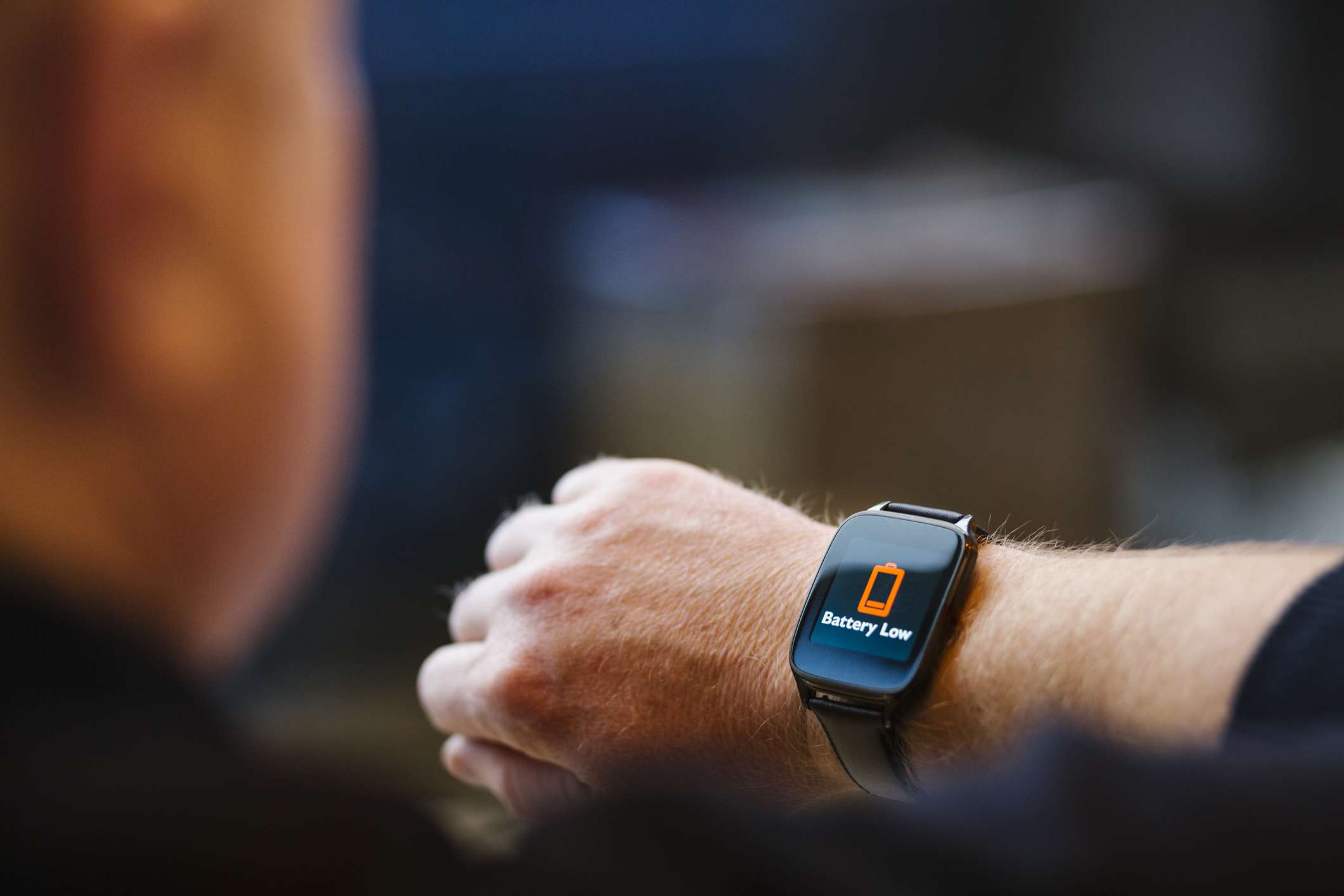Someone wearing a smart watch with a low battery signal displayed on the face of it.