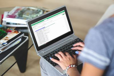 Woman using Google Sheets on a small laptop.