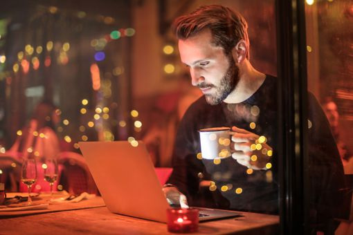 A man working on a laptop in a cafe at night.