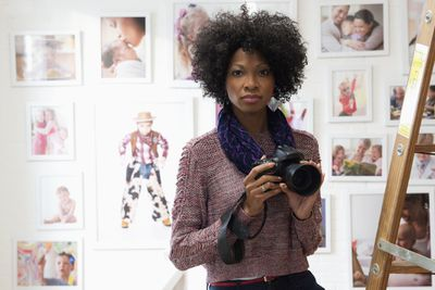 A female photographer holding a camera with portraits in the background.
