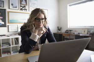 A woman is sitting at a desk looking at a laptop computer.