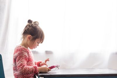 A photo of a toddler girl playing with a tablet.