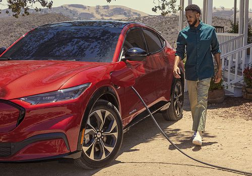Man standing next to his Ford EV