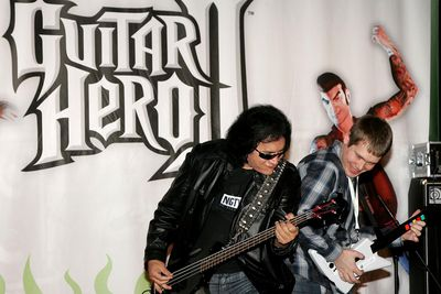 NEW YORK - APRIL 11: Musician Gene Simmons plays guitar with Guitar Hero II champion J.W. McNay at Virgin Megastore in Times Square to help launch Guitar Hero II on XBOX 360 on April 11, 2007 in New York City