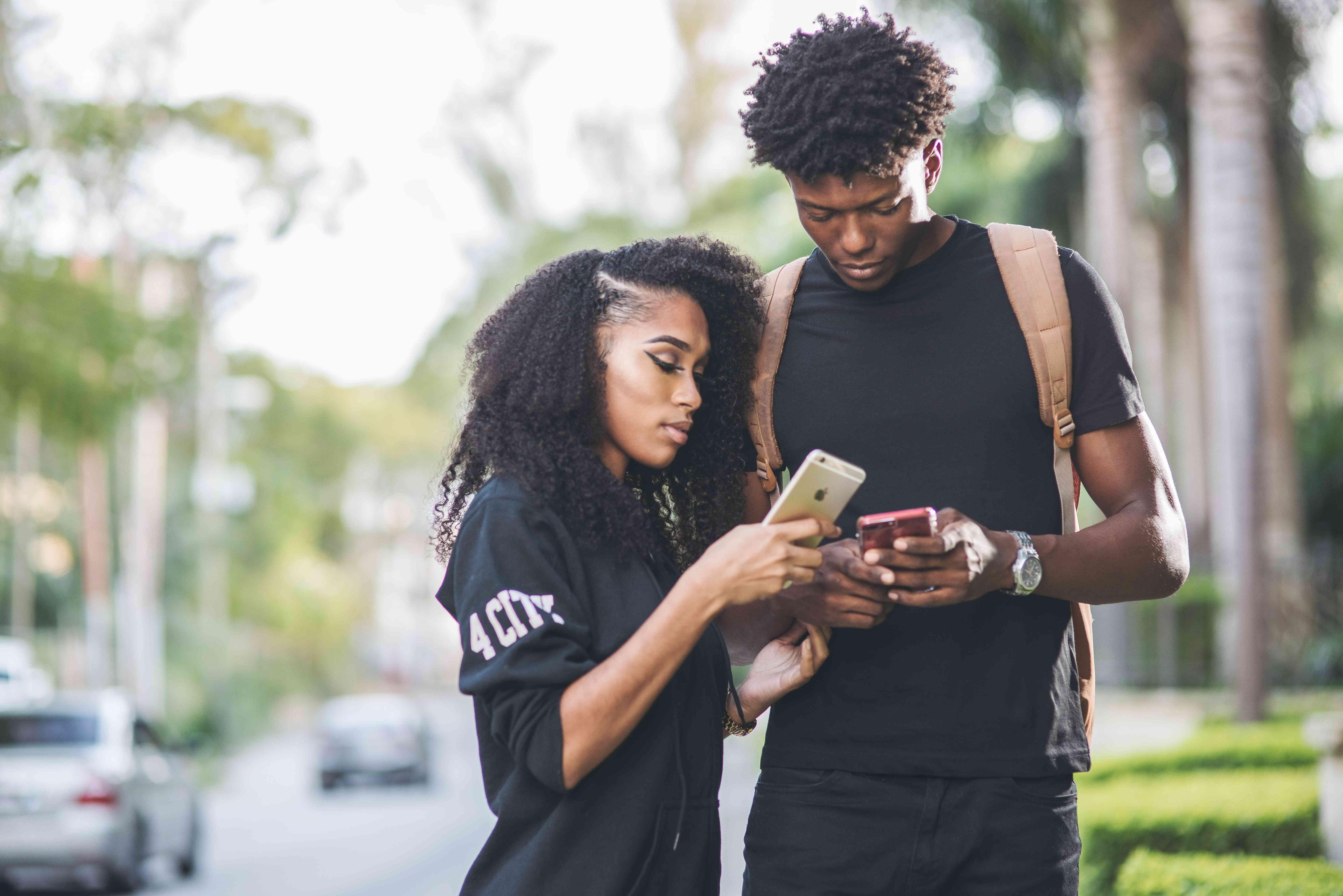 A couple using smartphones outdoors on a busy street.