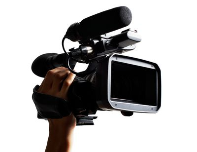 Hand holding professional HD broadcast camcorder as used in TV production.