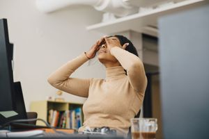 Image of a programmer with her hands rubbing her eyes