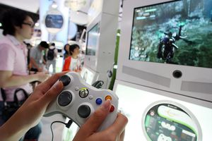 Visitors play with the XBOX 360 at the Microsoft booth