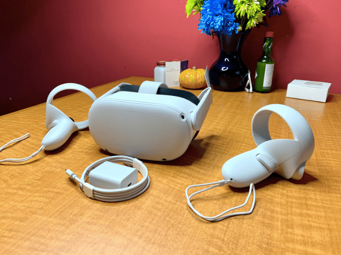 Oculus Quest 2, controllers, and charging cable on a table