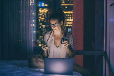 Woman using laptop and phone sitting on bed drinking coffee