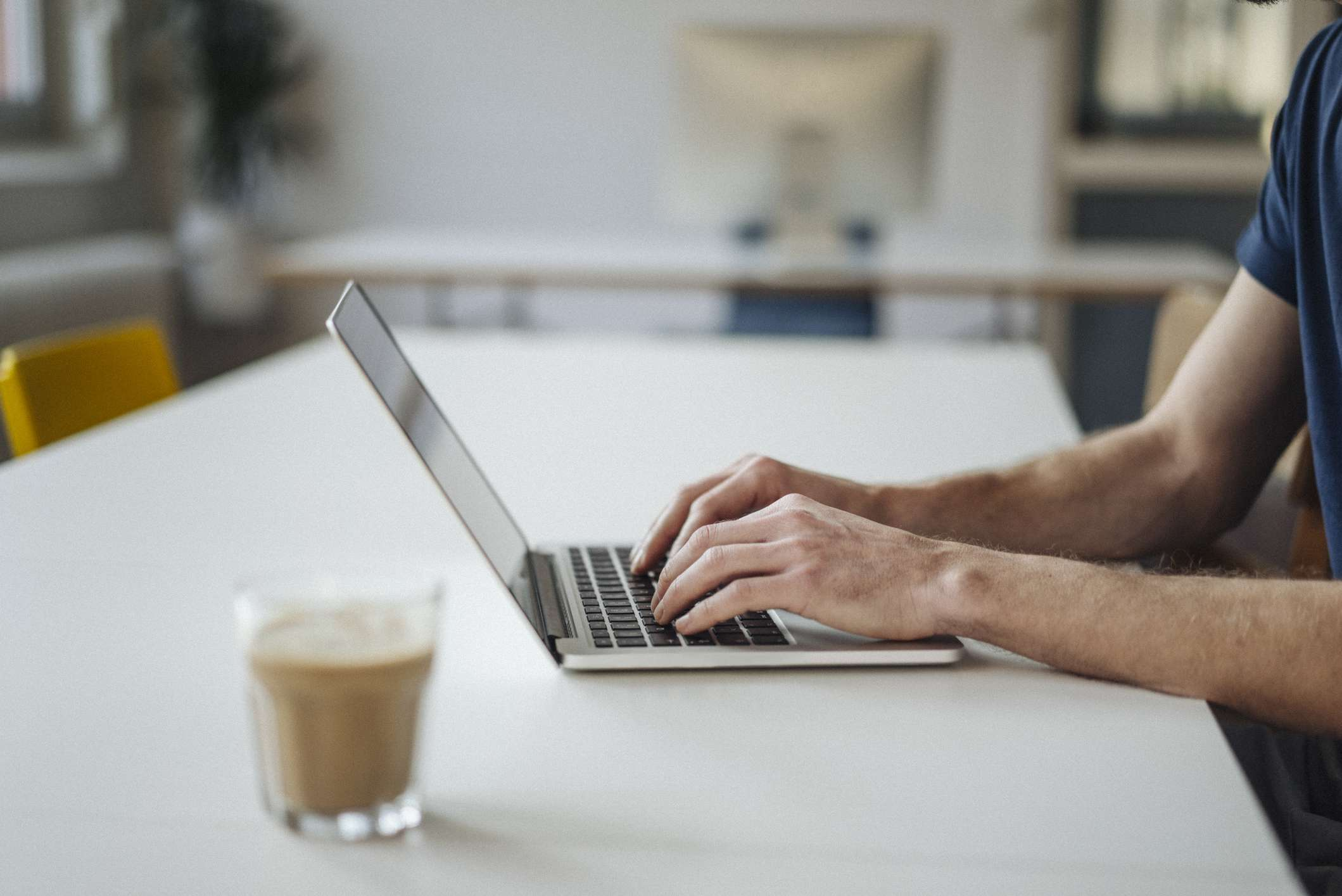 Man typing on laptop in coffee shop