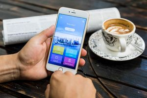 A close-up stock photo of a person's hands while holding an iPhone as he browses a colorful, unknown app. The hands and phone are resting on a wooden table with cup of coffee and newspaper in the background.