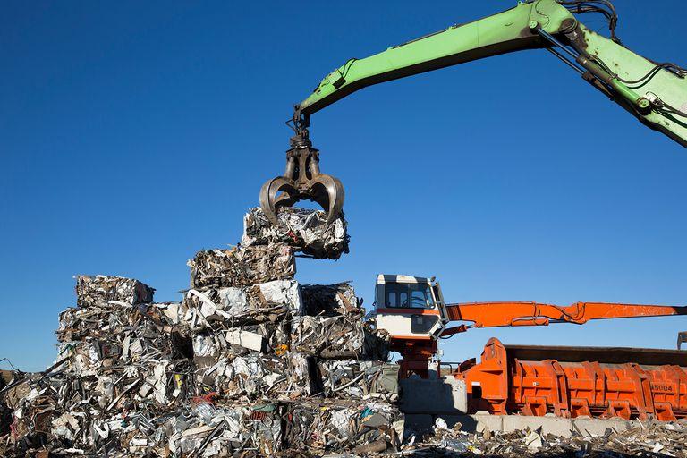 Crane lifting compressed trash at garbage dump