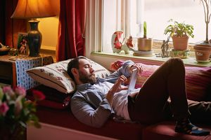 Man using Amazon Fire tablet on couch