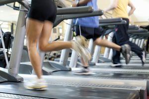 Blurred people running on treadmill