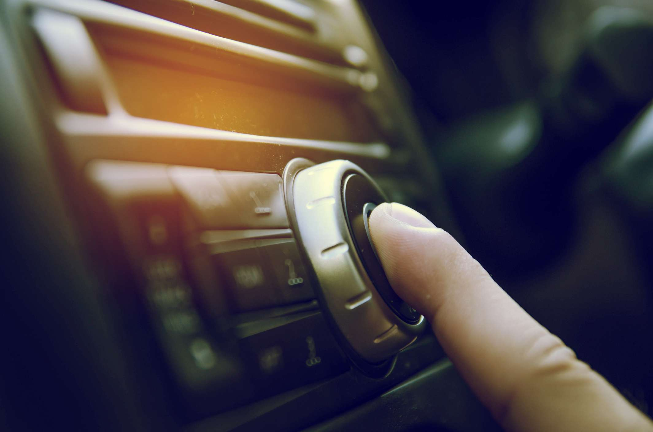 Person fiddling with a car radio.