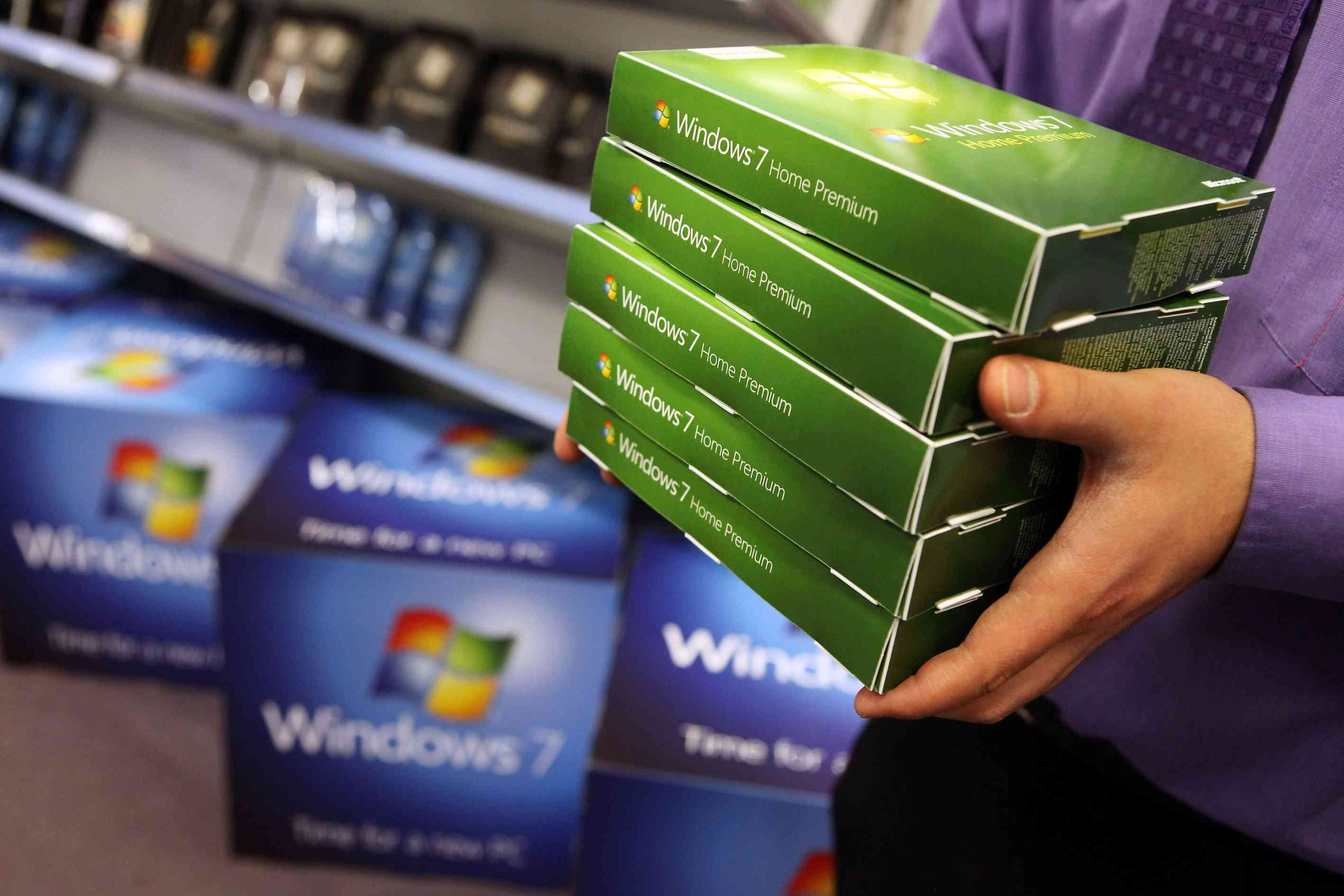 Person holding Windows 7 software boxes