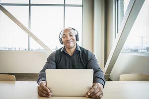 Businessman using laptop in office wearing headphones