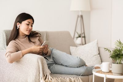 A woman sitting on the couch, listening to AirPods