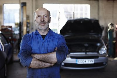 Mechanic standing in front of a blurred car in background.